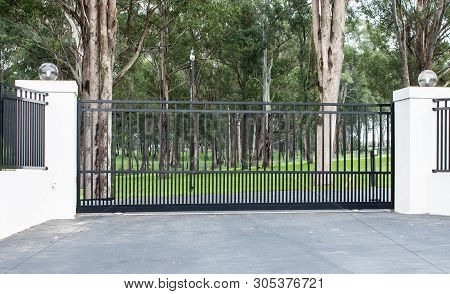 Metal Driveway Rural Property Entrance Gates Set In Brick Fence With Lights And Eucalyptus Gum Trees