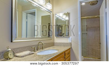Panorama Frame Vanity Unit With Brown Wooden Cabinets And Bright Lights Inside A Bathroom