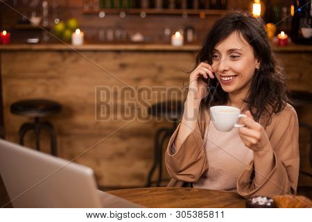 Cheerful Business Woman Smilng And Looking At Her Laptop In A Coffee Shop