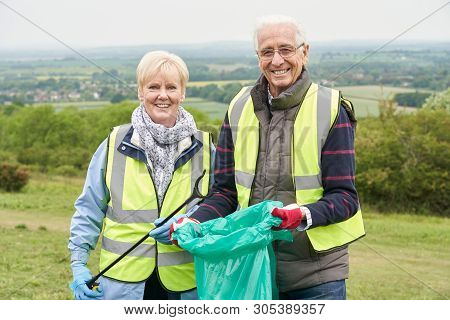 Portrait Of Helpful Senior Couple Collecting Litter In Countryside
