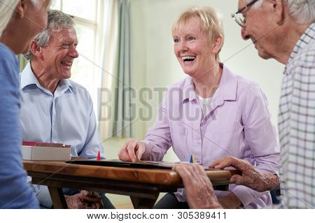 Group Of Retired Friends Playing Board Game At Social Club