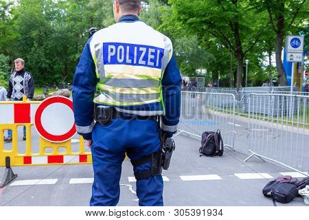 Hanover / Germany - May 25, 2019: German Police Officer Stands On A Street To Secure An Event. The G