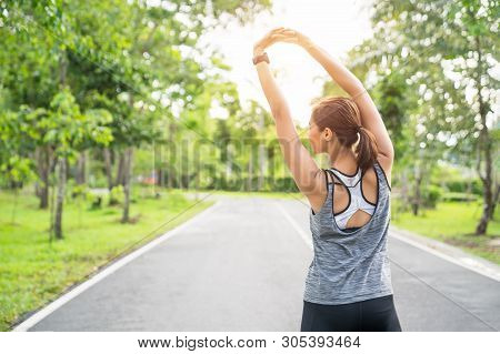 Young Female Runner Stretching Arms Before Running At Morning. Women Stretching For Warming Up Befor