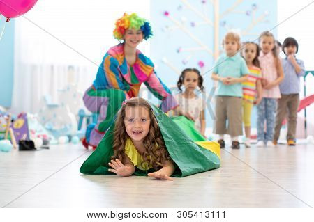 Kids Playing With Clown On Birthday Party In Entertainment Centre. Little Girl Climbing Through Tunn