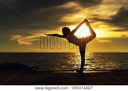 Abstrac.Silhouette yoga.Portrait of young woman practicing yoga at the sea.Relax at the sea.Meditati
