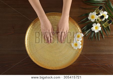 Woman soaking her hands in bowl with water and flowers on wooden table, top view. Spa treatment poster