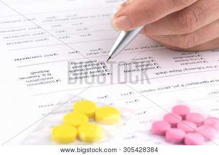 Colorful Pills And Hand Writing On Medical Questionnaire Form.