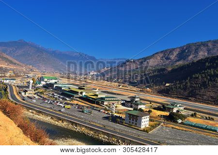 Paro Airport In The Mountains - Bhutan. Mountain Landscape With Village And Mini Airport.