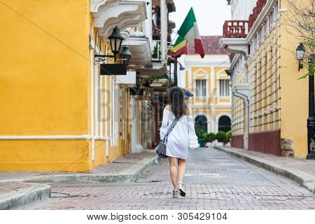 Beautiful Woman On White Dress Walking Alone At The Streets Of The Colonial Walled City Of Cartagena
