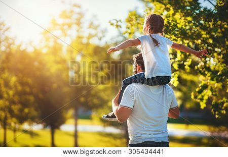 Concept Of Father's Day! Happy Family Dad And Child Daughter Back  In Nature