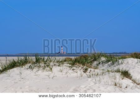 Westerheversand Lighthouse In A Distant. View From Sankt Peter-ording Beach In North Germany
