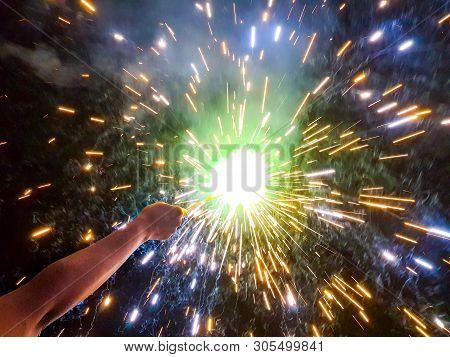 Hand Charki, A Hand Firework Emitting Circular Sparks In Black Background