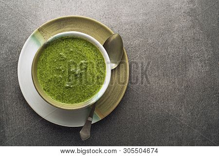 Spring Healthy Food. Green Creamy Soup With Vegetables And Herbs On Gray Background