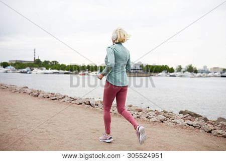 Rear View Of Blonde Sportswoman In Activewear Listening To Music In Headphones While Jogging Along W