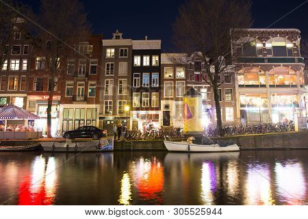 Amsterdam Canals In Old City At Dusk, With Illuminated Houses Reflected In Water, Amsterdam, Netherl