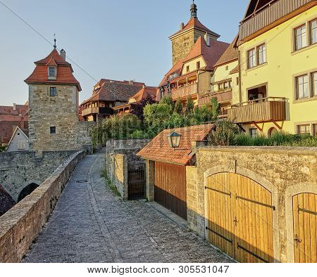 Rothenburg, Germany - Aug 2015: Golden Sunset Reflecting Off Medieval Homes Next To The Walkway On T