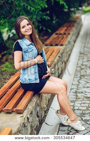 Beautiful Smiling Pregnant Woman In A Black Tight Dress And Blue Jeans Jaket Sitting On The Branch A
