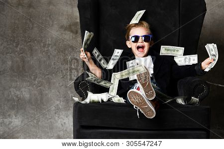 Happy Rich Kid Boy Millionaire Sits Under Money Rain Bills Falling In Big Luxury Armchair With Bundl
