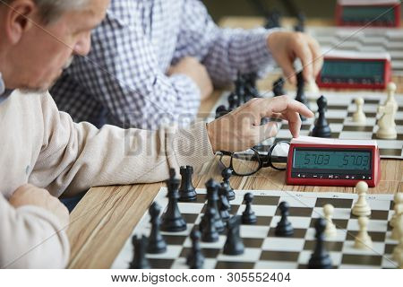Aged Grandmaster Carefully Pressing Chess Clock During Game At Amateur Chess Tournament