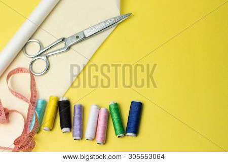 Sewing Accessories And Fabric On A Yelow Background. Sewing Threads, Pins, Pattern And Sewing Centim