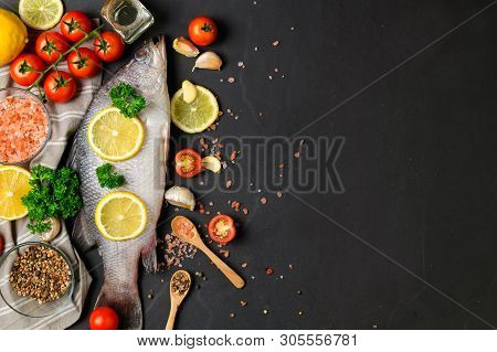 Fresh Fish Seabass And Ingredients For Cooking. Raw Fish Seabass With Spices And Herbs On Black Slat