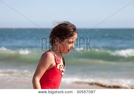 Little Girl Walking And Talking By The Ocean