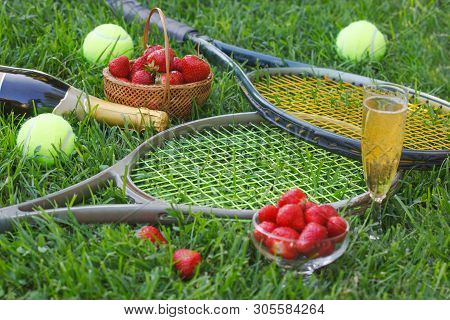 Strawberries With Whipped Cream, Glass With Champagne And Tennis Rackets And Balls On Grass. Wimbled