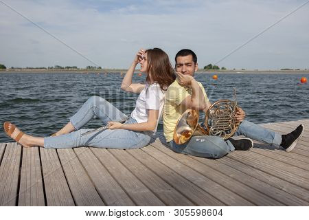 The Guy Playing The Horn And The Girl Playing The Flute On The Lake