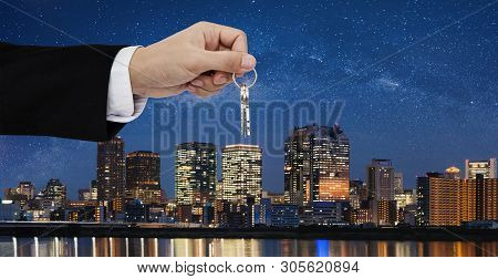 Real Estate Business, Residential Rental And Investment. Businessman Handover Keys, With City At Nig