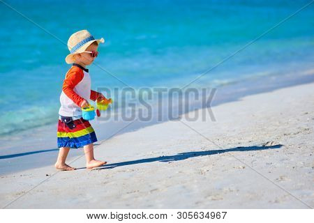 Two year old toddler boy playing with beach toys on beach
