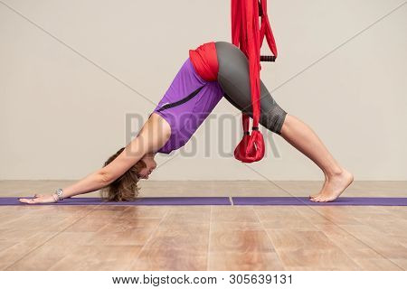 Khabarovsk, Russia - Apr 18, 2019: A Young Woman Is Practicing Aerial Inverse Anti-gravity Yoga With
