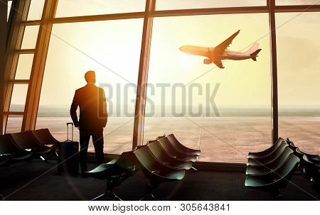 Businessman Standing At The Airport Window Waiting For Departure