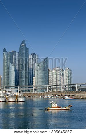 Busan, South Korea - April 2019: Minlaghang Fisherman Wharf Backgrounded By Skyscrapers Of Marine Ci