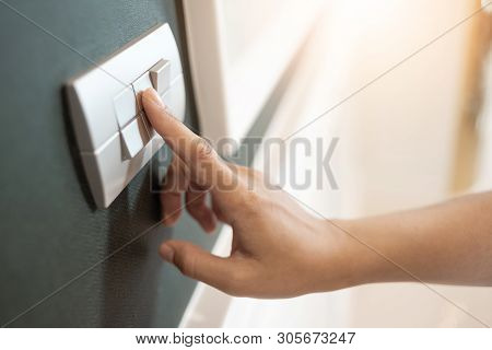 Close Up Of Female Finger Is Turning On Or Off On Light Switch Over Green Wall Covering. Copy Space.