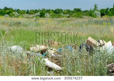 Odessa, Ukraine - June 08, 2019: Garbage Scattered In The Field Near The Forest. Pollution Of Nature