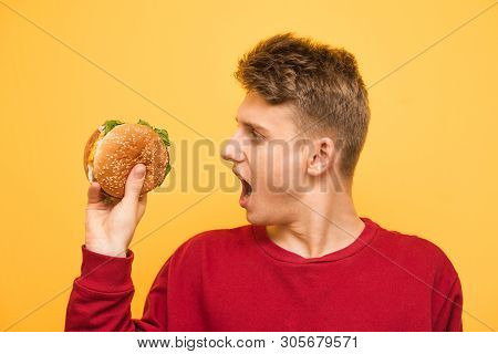 Hungry Guy Holds An Appetizing Burger In His Hands And Reacts Emotionally. Close Up Portrait Of A Su