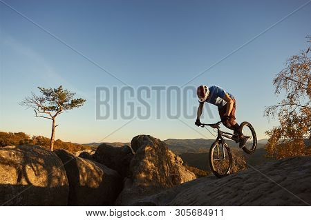 Professional Cyclist Balancing On Front Wheel On Trial Bike. Sportsman Rider Making Acrobatic Trick