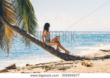 Traveler girl relaxing on tropical beach. Young girl traveler relaxing in vacation. Traveler relaxing on tropical beach in vacation. Girl in vacation relaxes on beach in summer day. Traveler. Summer. Vacations. Woman relaxing on the beach. .Vacation lifes