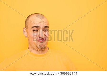 Funny Guy In Earrings And A Bald Head On His Head Wearing A Yellow Casual Dress, Makes A Funny Face