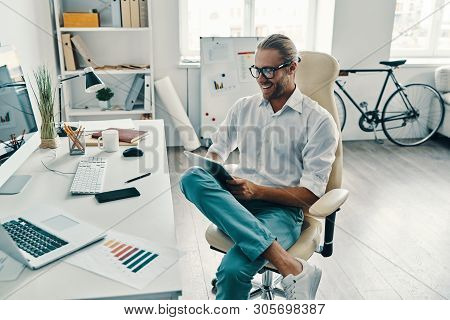 Confident Businessman. Top View Of Good Looking Young Man In Shirt Using Digital Tablet And Smiling