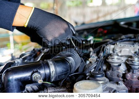 Auto Mechanic Is Filling The Engine Oil.auto Mechanic Preparing For The Work.
