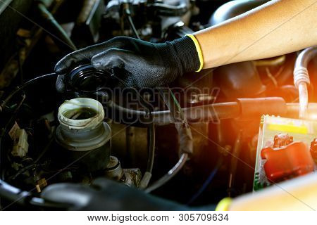 The Mechanic Is Checking The Brake Fluid Level Of The Engine.the Repairman Is Opening The Lid Of The