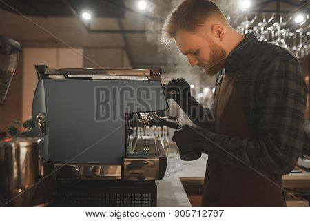 Barista Steaming Milk In Pinscher. Portrait Of Bearded Concentrated Barista Preparing Cappuccino In