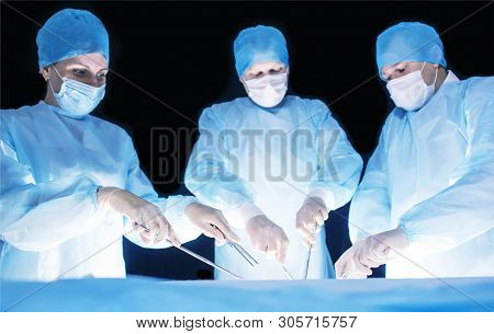 Three Surgeons, A Man And A Woman, Perform Surgery In The Operating Room To Remove And Transplant Hu