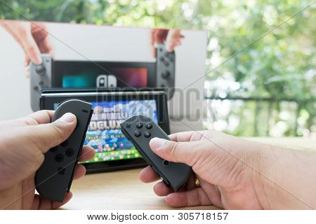 Bangkok, Thailand - June 10, 2019 : Hands Holding Nintendo Switch Gaming Controllers For Playing Dig