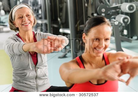 poster of Senior woman with personal fitness trainer stretch out at gym