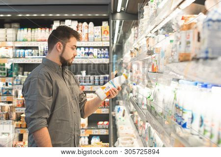 Man Is In The Milk Department Of A Supermarket, Holding A Bottle Of Milk In His Hand And Reading A L