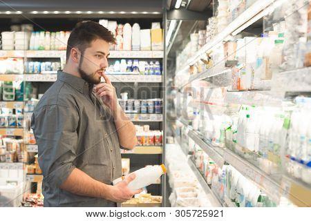 Portrait Of A Pensive Man Standing In The Supermarket Dairy Department, Looks At Shelves With Bottle