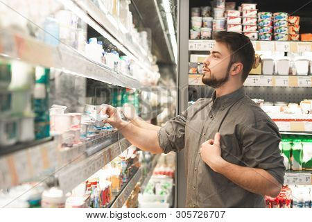 Happy Man Wearing A Shirt Stands At The Refrigerator In The Milk Department Of The Supermarket And T