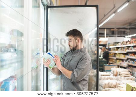 Buyer Breaks The Refrigerator Door In The Supermarket, Holds The Package In His Hands And Looks At T